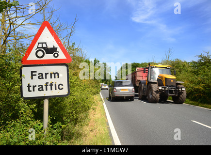 tractor and trailer passing warning sign of farm traffic in road ahead yorkshire united kingdom - Stock Photo