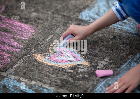 Young child drawing a colorful chalk heart on a stone sidewalk. - Stock Photo