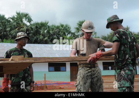 U.S. Navy Builder 3rd Class Daniel P. Fullerton, second from right, measures prefabricated column forms for new - Stock Photo