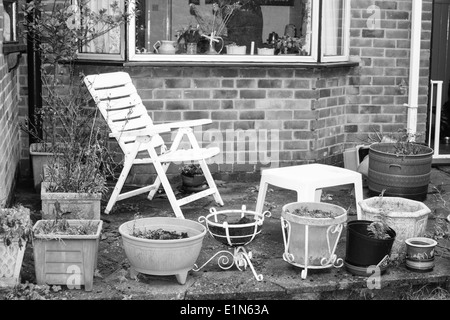 old tired looking garden with empty chair - Stock Photo