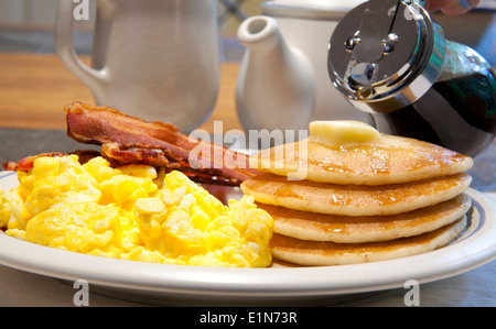 Breakfast of pancakes, scrambled eggs and bacon on a white plate being covered in maple syrup - Stock Photo
