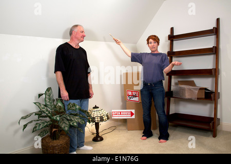 Woman gesturing to man with a paint brush standing among moving boxes in their new home - Stock Photo