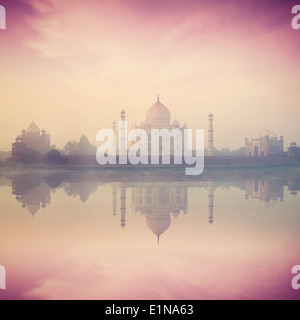 Vintage retro hipster style image of Taj Mahal on sunrise sunset reflection in Yamuna river panorama in fog, Indian - Stock Photo