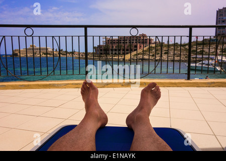 Man relaxing on an hotel balcony sunbed. - Stock Photo