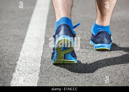 Runner feet running on stadium closeup on shoe - back view. - Stock Photo