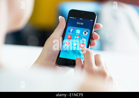 Woman looking on social media applications on a brand new black Apple iPhone 5S, which is designed and developed - Stock Photo