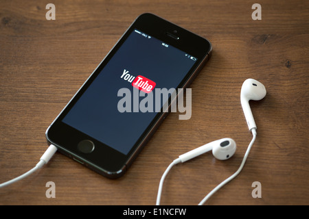 Brand new Apple iPhone 5S with YouTube application service on the screen lying on a desk with headphones. - Stock Photo