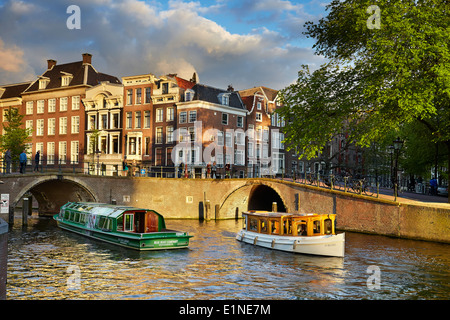 Tourist boat at Amsterdam bridge canal - Holland, Netherlands - Stock Photo