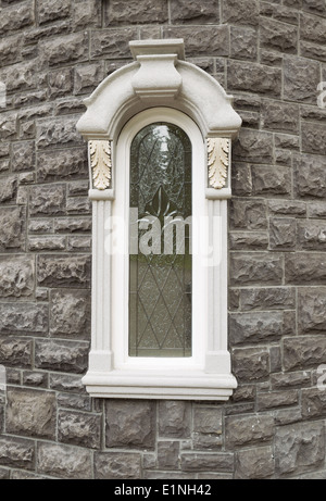 Vertical photo of brand new custom home window with stone structure in background - Stock Photo