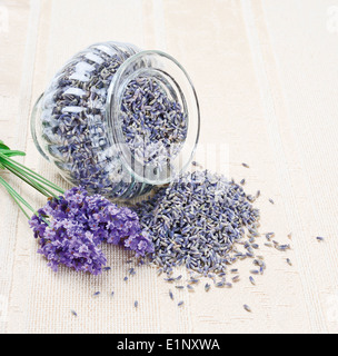 Lavender Flowers Fresh And Dry in a open glass on canvas next to a posy of fresh lavender - Stock Photo