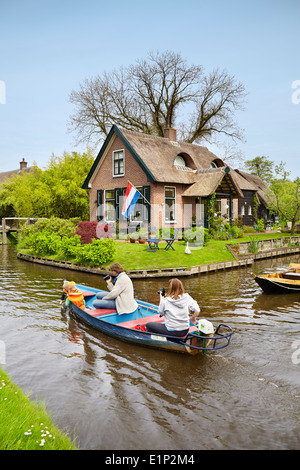 Tourists on the boat sail on the canal, Giethoorn village - Holland Netherlands - Stock Photo
