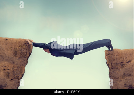 businessman overstretched between a rock and a hard place - Stock Photo