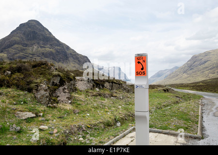 Roadside emergency SOS telephone beside a remote upland country road in mountains. Glen Coe Pass Highland Scotland - Stock Photo