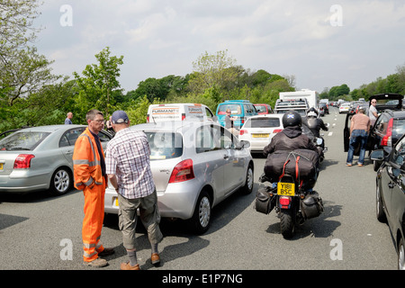 People standing on carriageway outside stationary vehicles in a traffic jam on M6 motorway due to accident causing - Stock Photo