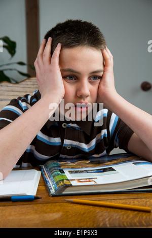A teenage boy is stressed doing homework. - Stock Photo