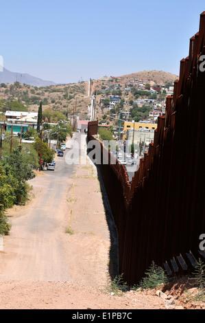 A metal wall, as seen from Arizona, marks the international border between Nogales, Arizona, USA, and Nogales, Sonora, - Stock Photo