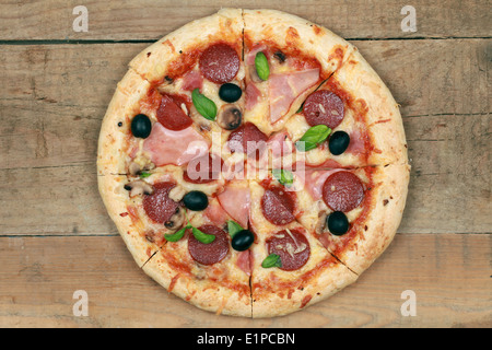 Deluxe Pizza with ham, pepperoni, mushrooms and olives - Stock Photo