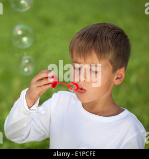 Boy having fun with bubbles on a green meadow. Shallow depth of field. - Stock Photo