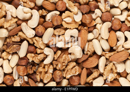 Collection of nuts such as peanuts, walnuts, almonds, hazelnuts, Brazil nuts and Macadamias forming a background - Stock Photo