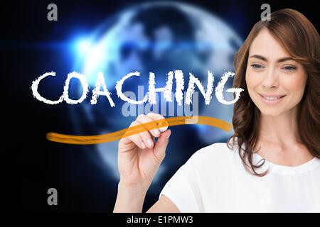 Businesswoman writing the word coaching - Stock Photo