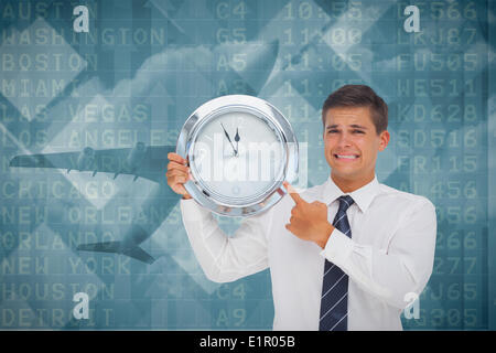 Composite image of anxious businessman holding and showing a clock - Stock Photo