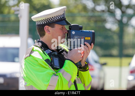 Police officer using hand held speed gun. - Stock Photo