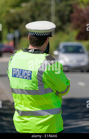 Back view of Police officer using hand held speed gun. - Stock Photo