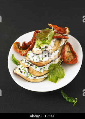 Eggplant and herb fromage frais mille-feuille with sun-dried tomatoes - Stock Photo
