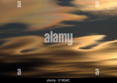 Altocumulus lenticularis clouds with rainbow colors at sunset - Stock Photo
