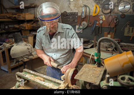 The aged man grinds out wood wares on a lathe in his joinery workshop. - Stock Photo