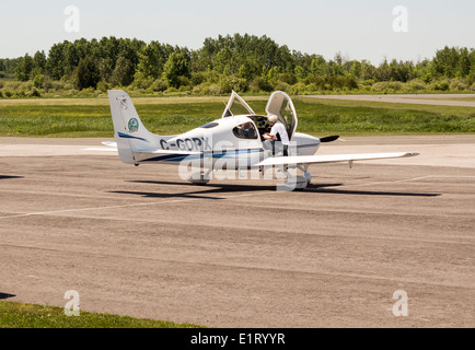 Pilot and passenger with foot on wing going over safety checklist on Cirrus SR20 aircraft at local airport - Stock Photo