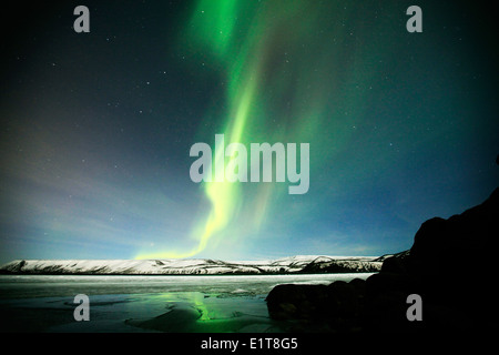 The Northern Lights shine above a frozen lake outside Reykjavik in Iceland - Stock Photo