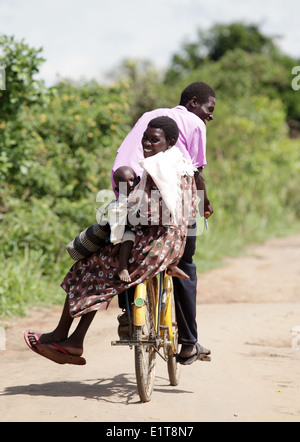 A family cycle in a rural part of the Lira district of northern Uganda. - Stock Photo