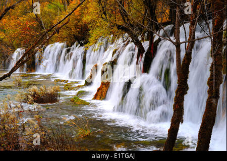 View a freshwater stream with waterfall a walking path in autumn in JiuZhaiGou National Park in Sichuan Province - Stock Photo