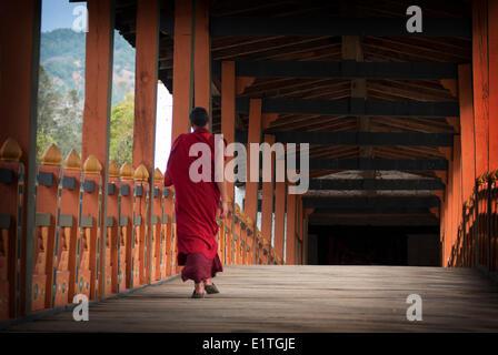 A monk walks across a bridge on his way to Phunaka Dzong near Punakha, Bhutan. - Stock Photo