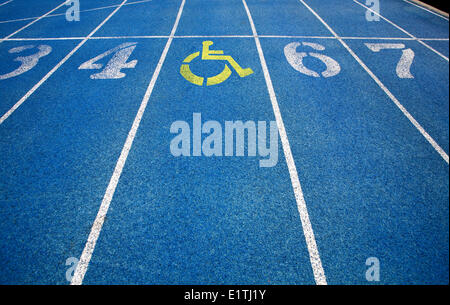 Handicap wheelchair icon superimposed on top of running track. - Stock Photo