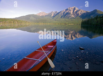 Red canoe on shore at Pyramid Lake, Jasper National Park, Alberta, Canada. - Stock Photo