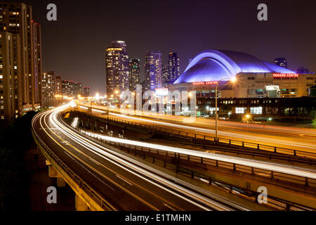 Evening view the Gardiner Expressway the Rogers Centre (formerly called the Skydome) lit with purple lights in downtown - Stock Photo