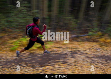 A young, fit woman trail running the Highline trail in Canmore, AB - Stock Photo