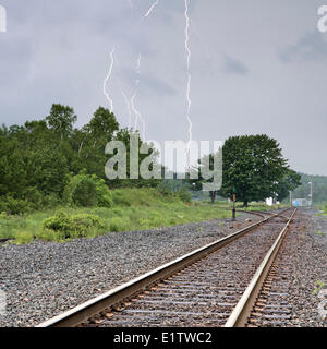 Multi-bolt cloud to ground lightning strike over railroad train tracks in Windsor Junction Nova Scotia as a summer - Stock Photo