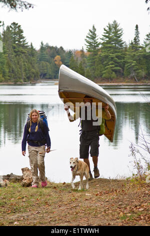 Young couple portage canoe from small lake in northwestern end of Algonquin Park, Ontario, Canada. - Stock Photo