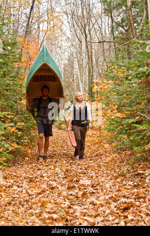 Young couple portage canoe  in northwestern end of Algonquin Park, Ontario, Canada. - Stock Photo
