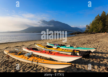 Kayaks line the beach on Vargas Island with the Cat Face Range in the background, Clayoquot Sound, British Columbia, - Stock Photo
