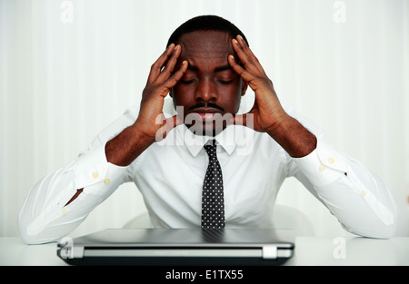Pensive african businessman sitting at his workplace in office - Stock Photo