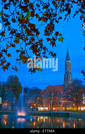 Martinskirche (St Martin's Church) bell tower a fountain fringed by trees along the bank the Isar River City Landshut - Stock Photo