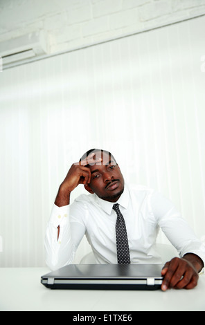 African businessman sitting at his workplace in office - Stock Photo