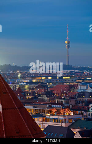 View towards the Olympiaturm (Olympic Tower) over the rooftops buildings at sunset in the City München (Munich) - Stock Photo