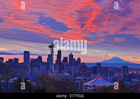 Seatlle skyline at sunrise on a cold early winter morning with beautiful snow coverred Mount Rainier in the background - Stock Photo