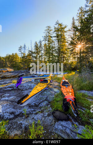 Kayaks rest above the high tide mark on Octupus Island Provincial Marine Park, British Columbia, Canada - Stock Photo