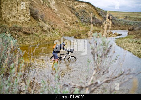 A man pushes his mountain bike through spring run off conditions on the Maah Daah Hey Trail, North Dakota - Stock Photo